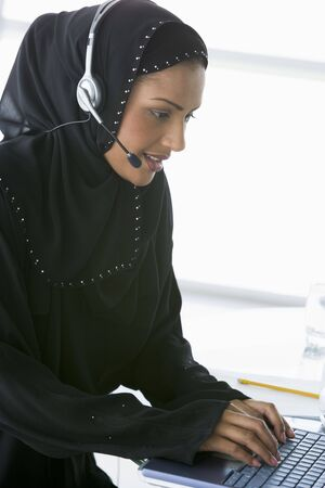 Woman wearing headset with laptop smiling (high key/selective focus) Stock Photo - 3171223