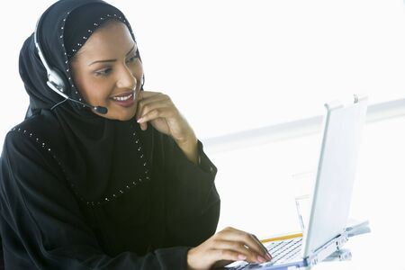 Woman wearing headset with laptop smiling (high key/selective focus) Stock Photo - 3171205