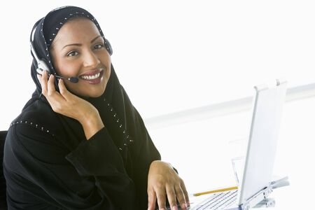 handsfree telephones: Woman wearing headset with laptop smiling (high keyselective focus) Stock Photo