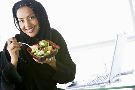 jilaabah: Woman eating salad near laptop smiling (high keyselective focus)