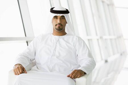 khameez: Man sitting indoors (high keyselective focus)