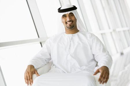 khameez: Man sitting indoors smiling (high keyselective focus)