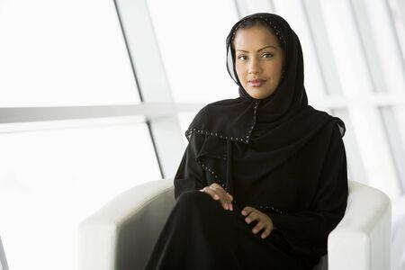 jilaabah: Woman sitting indoors smiling (high keyselective focus)