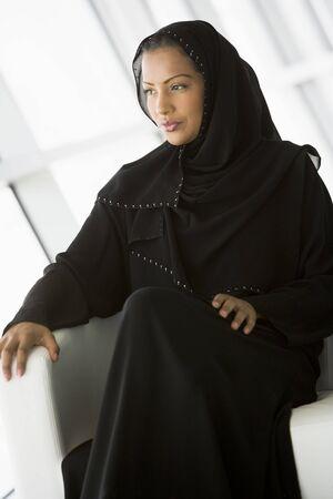 jilaabah: Woman sitting indoors (high keyselective focus)
