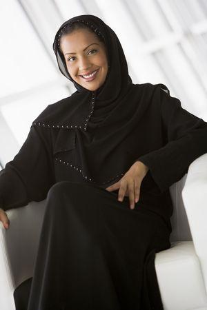 windowpanes: Woman sitting indoors smiling (high keyselective focus)