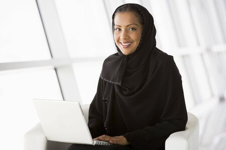 Woman sitting indoors with laptop smiling (high key/selective focus) Stock Photo - 3171256
