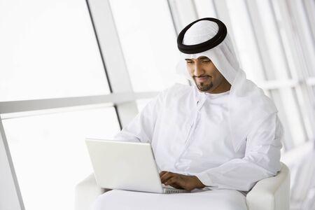 thobes: El hombre con el ordenador port�til en interiores sonriente (clave de alta  selectiva enfoque)