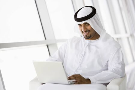 dishdasha: Man indoors with laptop smiling (high keyselective focus)