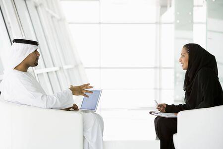 thobes: Dos hombres de negocios en interiores con un ordenador port�til de hablar y sonre�r (clave de alta  selectiva enfoque)