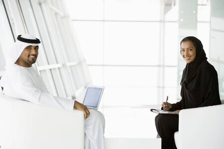 Two businesspeople indoors with a laptop smiling (high keyselective focus)