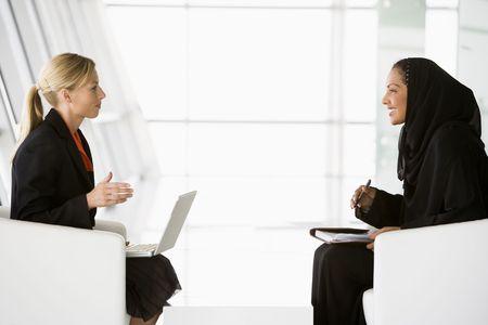 dos personas hablando: Dos mujeres empresarias en interiores con un ordenador port�til de hablar y sonre�r (clave de alta  selectiva enfoque)  Foto de archivo