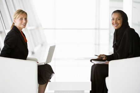 Two businesswomen indoors with a laptop smiling (high keyselective focus)