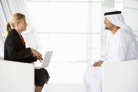 Two businesspeople indoors with a laptop talking and smiling (high keyselective focus)