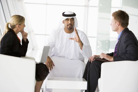 Three businesspeople indoors with a laptop talking and smiling (high key/selective focus) Stock Photo - 3171259