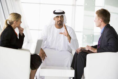thawbs: Tres hombres de negocios en interiores con un ordenador port�til de hablar y sonre�r (clave de alta  selectiva enfoque)