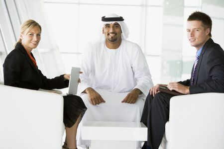 Three businesspeople indoors with a laptop smiling (high keyselective focus)