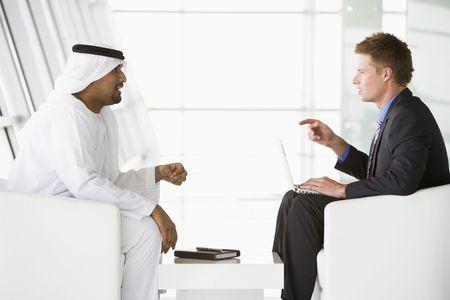 thawbs: Dos hombres de negocios en interiores con un ordenador port�til de hablar y sonre�r (clave de alta  selectiva enfoque)