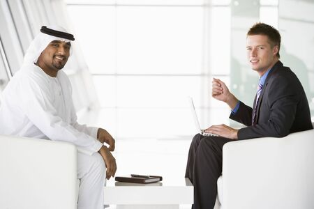 Two businessmen indoors with a laptop talking and smiling (high keyselective focus)