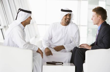 Three businessmen indoors with a laptop talking and smiling (high keyselective focus) photo