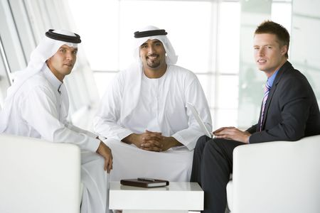 Three businessmen indoors with a laptop smiling (high keyselective focus)
