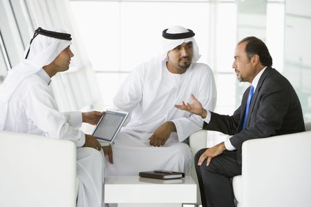 Three businessmen indoors with a laptop talking (high keyselective focus) photo