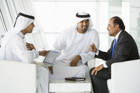 Three businessmen indoors with a laptop talking and smiling (high keyselective focus) Stock Photo