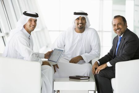 Three businessmen indoors with a laptop smiling (high keyselective focus) photo