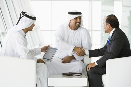 Three businessmen indoors with a laptop shaking hands and smiling (high keyselective focus)