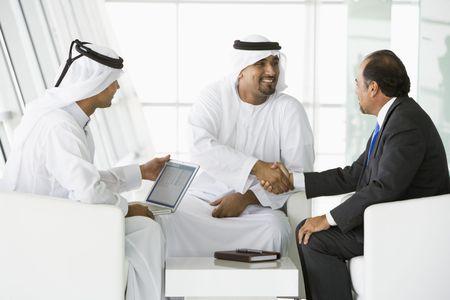 thawbs: Tres hombres de negocios en interiores con un ordenador port�til de agitar las manos y sonriendo (clave de alta  selectiva enfoque)