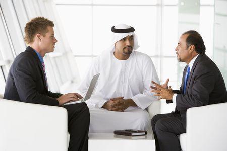 business man laptop: Tres hombres de negocios en interiores con un ordenador port�til de hablar y sonre�r (clave de alta  selectiva enfoque)