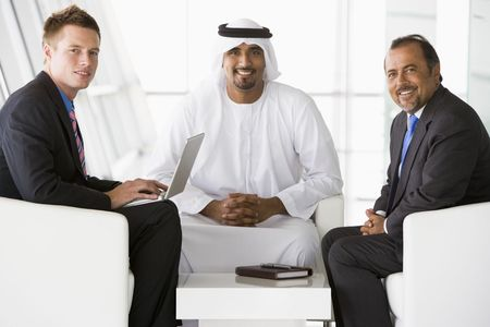 Three businessmen indoors with a laptop smiling (high key/selective focus) Stock Photo - 3174724
