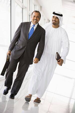 thobes: Dos hombres de negocios a pie en un pasillo y sonriente (clave de alta  selectiva enfoque)