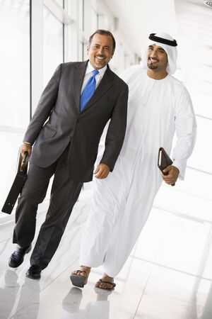 Two businessmen walking in a corridor and smiling (high keyselective focus) photo