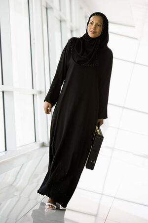 jilaabah: Businesswoman walking in a corridor with a briefcase and smiling (high keyselective focus)