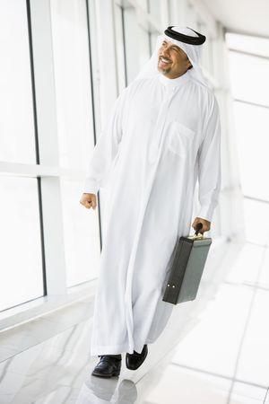 thawbs: Empresario caminar en un pasillo con un malet�n sonriente (clave de alta  selectiva enfoque)