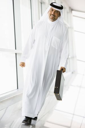 thawbs: Empresario caminar en un pasillo con un malet�n sonriente (clave de alta  selectiva enfoque)  Foto de archivo