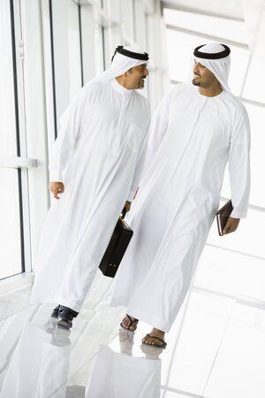 dishdasha: Two businessmen walking in a corridor talking and smiling (high keyselective focus)
