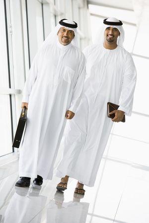 thawbs: Dos hombres de negocios a pie en un pasillo sonriente (clave de alta  selectiva enfoque)  Foto de archivo