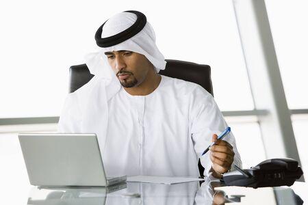 thobes: Empresario en el cargo con el ordenador port�til de trabajo (clave de alta  selectiva enfoque)