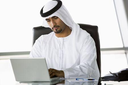 thawbs: Empresario en el cargo con el ordenador port�til de trabajo (clave de alta  selectiva enfoque)