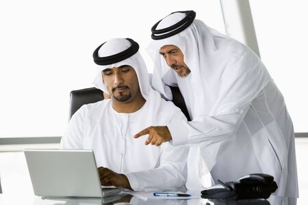 Two businessmen in office pointing at laptop (high keyselective focus)