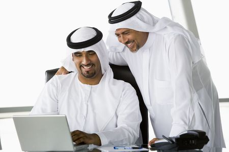 dishdashas: Two businessmen in office with laptop smiling (high keyselective focus)