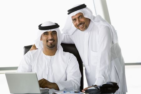 Two businessmen in office with laptop smiling (high keyselective focus)