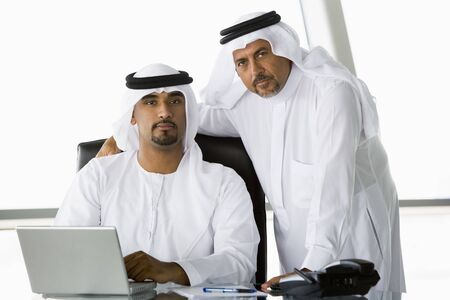 egal: Two businessmen in office with laptop (high keyselective focus) Stock Photo