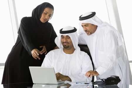 thawbs: Tres hombres de negocios en el cargo con el ordenador port�til y apunta sonriente (clave de alta  selectiva enfoque)