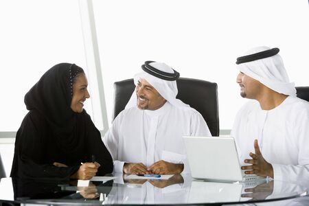 Three businesspeople in office with laptop talking and smiling (high keyselective focus)