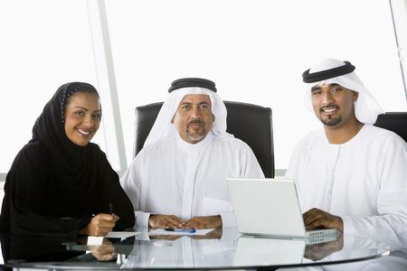 Three businesspeople in office with laptop smiling (high keyselective focus) Stock Photo