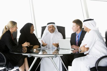 Five businesspeople in office with laptop talking and smiling (high keyselective focus) Stock Photo