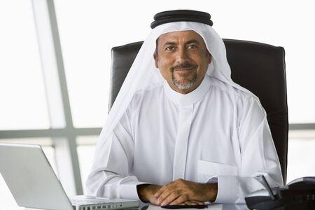 khameez: Businessman in office with laptop smiling (high keyselective focus)