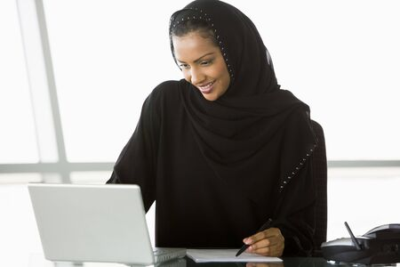 Businesswoman in office with laptop writing and smiling (high key/selective focus) Stock Photo - 3171198